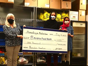 Lori McRitchie (from left to right) accepts a $1,000 cheque from Sairah and Mahrosh Khan of the Ahmadiyya Muslim Women's Association following the group's fundraising effort throughout Ramadan. Photo by Riley Cassidy / The Airdrie Echo