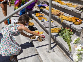 A youngster places a pair of moccasins on the steps of the former Mohawk Institute residential school on Sunday May 30, 2021 in Brantford, Ontario. People gathered to honour the memory of the lives of 215 children whose remains were discovered in a mass grave at a Kamloops (B.C.) Indian Residential School.
