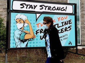 Sherry Tanney, a personal support worker at Brockville General Hospital, walks past a sign on the hospital grounds offering encouragement to front-line workers amid the COVID-19 pandemic on Monday afternoon. (RONALD ZAJAC/The Recorder and Times)
