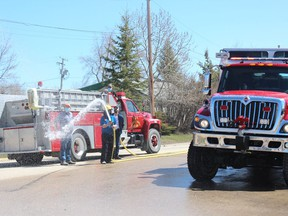 After hosing down the new truck, retired members of Carrot River Fire and Rescue attempt to hose down some of the audience as the department marked the retirement of one truck and commissioning of a brand new one. Photo Susan McNeil.