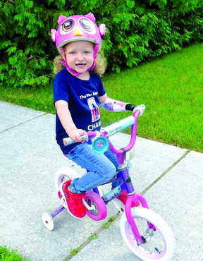 Michaela rides her bike with the help of a special device. PHoto supplied.