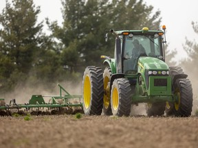 A farmer uses a cultivator on a small field destined to be planted with corn.