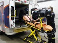 Timmins paramedics Natalie Robitaille and Ryan Roy check their equipment while loading a stretcher into an ambulance at the Cochrane District Social Services Administration building. Cochrane District is one of nine regions across the province approved for a pilot program that will see paramedics extending services to palliative care patients.  RICHA BHOSALE/The Daily Press