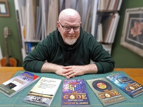 """Dwayne James shows off the many books that he has written. He has a few more in his """"Code"""" series.TP.jpg"""