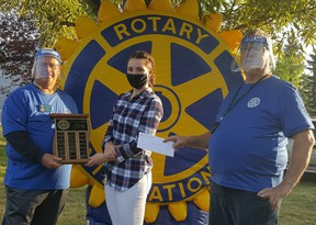 Rotarian Stew Hennig, Fort High 2020 valedictorian Karissa Goulding, and Ted Griffiths pose for a photo as Goulding accepts a scholarship from the Fort Saskatchewan Rotary Club last year. The local Club is offering two $1,000 scholarships to two local graduates again this year. Photo Supplied.