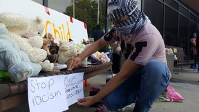 Mohammad Alowdh puts up signs during a drive-by vigil held at the Chatham-Kent Civic Centre on Wednesday in honour of the Afzaal family, who were killed in an alleged hate-motivated attack in London last Sunday. (Trevor Terfloth/The Daily News)