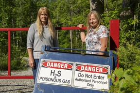 Paula Jongerden and Richelle Spanjers by a sign next to their properties in Norfolk County warning of the putrid smell coming from an old natural gas well about 300 metres away that erupts at least twice a week.