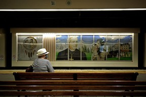 A woman waits for a train at the Grandin LRT Station in Edmonton. In background is a mural depicting the residential school system and Catholic church Bishop Vital-Justin Grandin. Edmonton city council voted unanimously on Monday June 7, 2021 to change the name of the Grandin LRT Station and cover up this mural as soon as possible, following the recent discovery of 215 children who were found in a mass grave on the grounds of a former residential school in Kamloops, B.C.