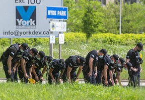 Eleven London police officers search for evidence along the southbound lanes of Hyde Park Road near South Carriage Road in northwest London as part of the investigation into a crash Sunday night that killed three adults and a teen who were walking. Photograph taken on Monday June 7, 2021 (Mike Hensen/The London Free Press)
