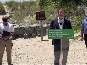 Prince Edward County Mayor Steve Ferguson, left, and Bay of Quinte MPP Todd Smith flank Environment, Conservation and Parks Minister Jeff Yurek during Thursday's announcement at Sandbanks Provincial Park.