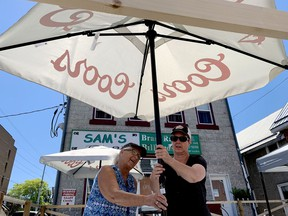 Sam Major, left, owner of Sam's Brass Rack on Perth Street, and her daughter, manager Trish Tye, prepare the establishment's patio on Thursday for Friday morning's Stage One reopening. (RONALD ZAJAC/The Recorder and Times)