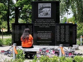 A visitor sits at the Walpole Island First Nation monument dedicated to the children from the community who attended Indigenous residential schools. The community will not be celebrating Canada Day this week. Mark Malone/Postmedia Network