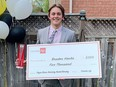 Kingston Frontenacs defenceman Braden Hache with his Hockey Gives Blood award and bursary cheque at his home in Newmarket on Wednesday.