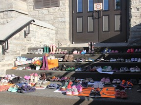 Approximately 200 childrens' shoes, boots and moccasins were placed on the steps of St. Columbkille's Cathedral in Pembroke Monday evening as a memorial to the 215 children whose remains were discovered on the grounds of a residential school in Kamloops, B.C.