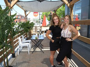 Valerie Fremlin, left, and Kelsey Cutinello, co-owners of La Fromagerie on Elgin Street, prepare their patio for opening on Friday. The Ford government announced on Monday that Ontario will move into Step One of its reopening plan on Friday at 12:01 a.m., three days ahead of schedule. Step One includes allowing non-essential retail stores to reopen, and bars and restaurants to begin serving customers on their patios.