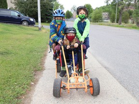 Davis Armstrong, 9, middle, gives Lex Armstrong, 6, left, and Gabriel Dion, 5, a ride in Copper Cliff, Ont. on Tuesday June 22, 2021. John Lappa/Sudbury Star/Postmedia Network