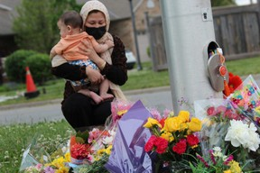 Nafisa Azima holds her son, Seena Safdari, after placing flowers Monday night on Hyde Park Road in London where five members of a Muslim family out for a walk were struck Sunday night by a pickup truck in what London police said was a targeted attack by the driver. Four family members died and the fifth, a nine-year-old boy, was injured. (Dale Carruthers, The London Free Press)