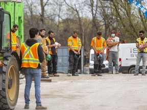 Workers pause for a moment of silence on April 28 at 555 Teeple Terrace in London, Ont. where two workers lost their lives last December and five were injured. Mike Hensen/Postmedia Network