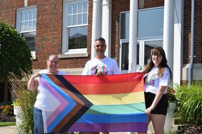 Strathroy Pride festival organizers Kelly Fleming, Frank Emanuele and Lauren Huston hold a rainbow pride flag outside Strathroy town hall, where it will be raised Saturday at 11 a.m. during the farmers' market. (Calvi Leon/The London Free Press)