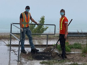 Municipal Employees, Mark Stopford and Owen Musselman, worked quickly to clear a plugged storm sewer in a rain storm. Glenn Hedley photo