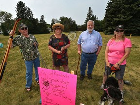 Displaying some of the activities done in the park, from left, Garry Trottier, Nancy Byway, John Thompson and Elaine Nystrom, are some members of a coalition of Idylwylde community members opposing the city's plan to add 18 trees to this pocket park in the community.