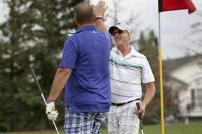 Chris MacConnell (right) and Vic Klassen from The Hamlets at Cedarwood Station high five each other after MacConnell sinks a putt in the Airdrie Chamber of Commerce Golf Classic at Woodside Golf Course on Friday August 14, 2015 in Airdrie, Alta. The annual fundraising tournament will benefit the Chamber and the Airdrie Health Foundation to support local health programs, education, facilities and equipment. Britton Ledingham/Airdrie Echo/Postmedia Network