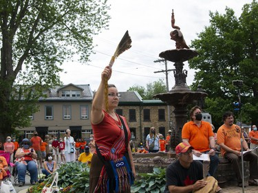 A sea of orange fills the grounds of Gananoque Town Hall  on Canada Day during  a memorial to reflect on the hundreds of unmarked gravesites that have been found across Canada. Clarice Gervais holds eagle feathers in the air while Donna Lynn Neil tells her story of her life and the hardships she has faced as an Indigenous person. (JESSICA MUNRO/Local Journalism Initiative)
