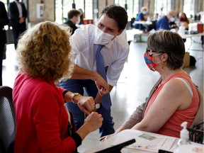 Not quite pressing the flesh: Prime Minister Justin Trudeau bumps elbows with people as he visits a COVID-19 vaccination clinic in Ottawa on July 2.