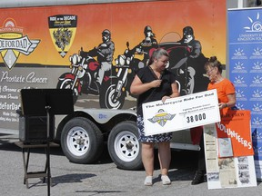 Kingston-Quinte Motorcycle Ride for Dad 2021 chair, Marion Perry, right, presents a grant of $38,000 to the University Hospitals Kingston Foundation and Dr. Katrina Gee, associate professor/researcher, Queen's University School of Medicine, for her work in fighting prostate cancer, at an announcement ceremony outside Cataraqiui Community Centre in Kingston on Friday.
