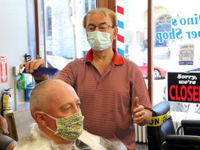 Dino Bartzis of Dino's Barber Shop combs the hair of Randy Conroy on June 12, 2020, after COVID-19 pandemic restrictions were eased in 2020, allowing barbershops to reopen. Bartzis died on Sunday, July 4, 2021.