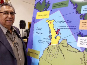 Former Saugeen First Nation chief Vernon Roote looked at a map outlining the treaties and the Bruce Peninsula land claim and aboriginal title claim to waterbeds in the traditional territory at the beginning of testimony in 2019 the James Mason Memorial Cultural and Recreation Centre at Saugeen First Nation.
