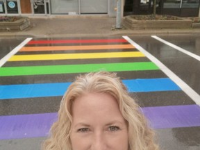 Oxford County Pride president Tami Murray stands in front of the rainbow crosswalk that was painted on Dundas Street near Museum Square this week in Woodstock.