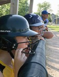 Leah Kelly (left) and Cambell Ward, along with coach AJ Moses, watch the action unfold between visiting Clinton and one of three Mitchell Squirt girls fastpitch softball teams July 26 at Keterson Park in Mitchell. The hometown Hornets dropped a close game, 19-15. ANDY BADER/MITCHELL ADVOCATE