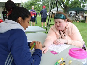 Polly Singh creates a henna tattoo for Shelby Emery during the 2018 Art in the Park, held in Mike Weir Park in Sarnia's Bright's Grove. File photo/Postmedia