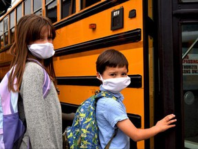 Two students wearing face masks board a school bus in this file photo. Top pediatric doctors are making several recommendations to ensure in-person school is as safe as possible. Postmedia file photo