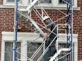 Jorge Rites, of Ottawa-based Simluc Contractors, walks down a scaffold as workers do a roofing job at Brockville Collegiate Institute on Wednesday afternoon. The work is being done ahead of a return to school next month.  (RONALD ZAJAC/The Recorder and Times)