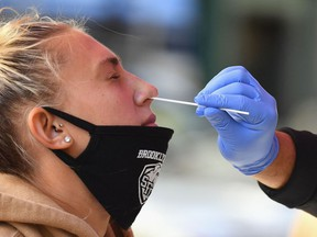 In this file photo a healthcare worker takes a nasal swab sample from a student to test for COVID-19.