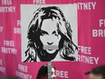 In this file photo taken on July 14, 2021 a woman holds a poster of Britney with her mouth taped shut as fans and supporters gather outside the Los Angeles County Courthouse in Los Angeles during a scheduled hearing in the Britney Spears guardianship case.