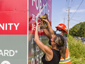 """Norfolk County mayor Kristal Chopp gets help from roads foreman Mike Evans affixing a """"Sold"""" banner on a real estate sign for the 25-acre HUB lands on Ireland Road in Simcoe on Friday September 3, 2021."""