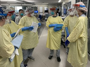 Registered nurses in the critical care ward of Brantford General Hospital huddle before entering a COVID-19 patient's room.