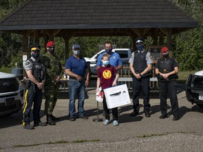 The Military Police, Royal Canadian Mounted Police and Cold Lake Peace Officers reward youth in the community for practicing safety during the summer at 4 Wing Cold Lake, Aug. 20, 2021. (Left to right backrow) Const. Andrew Kary, Corporal Collin Hickey, Warren Hobart, David Zimmerman, CPO Simon Crevier and Sgt. Angie Castle. (Front row) Simon Hare. Photo: Cpl Connie Valin/ 4 Wing Imaging