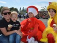 From left, mom Breanne Van Moorsel holds Gabe, 2, who enjoys an apple and new friends: Emily Swerdfeger, dressed as an apple, and Sierra Latulippe, dressed as a chicken, at the Iroquois Apple Festival on Saturday September 18, 2021 in Iroquois, Ont. Shawna O'Neill/Cornwall Standard-Freeholder/Postmedia Network