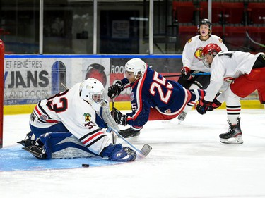 Cornwall Colts Kwami Julien diving over the blue ice as Brockville Braves goaltender Cannon Flageolle eyes the puck during exhibition play on Saturday September 11, 2021 in Cornwall, Ont. Cornwall won 6-1. Robert Lefebvre/Special to the Cornwall Standard-Freeholder/Postmedia Network