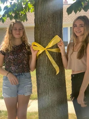 Addison Compagnion, left, and Amy Fraser tie a yellow around a tree for Friday's World Suicide Prevention Day.