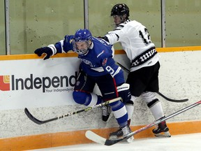 Greater Sudbury Cubs defenceman Carter Geoffroy (9) takes a hit from Espanola Express forward James Eng (13) during first-period NOJHL action at Gerry McCrory Countryside Sports Complex in Sudbury, Ontario on Thursday, September 16, 2021.