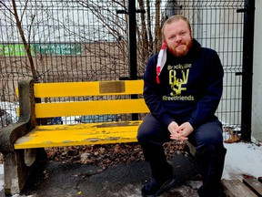 Leigh Bursey, a Brockville city councillor and homelessness awareness advocate, sits in late 2020 by a plaque at the city's downtown parkette, at the corner of King and John streets, in memory of a homeless man who died earlier this year, and to raise awareness of homelessness in the community.  (FILE PHOTO)