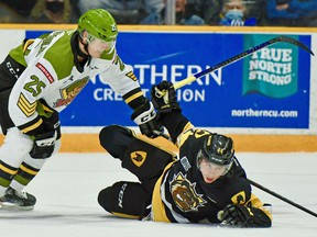Alex Christopoulos of the North Bay Battalion deals with Nathan Staios of the Hamilton Bulldogs in first-period Ontario Hockey League action, Thursday night. The Troops completed a four-game home stand. Sean Ryan Photo