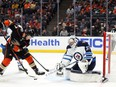 Mason McTavish #37 of the Anaheim Ducks skates the puck against Connor Hellebuyck #37 of the Winnipeg Jets in the second period at Honda Centre on Oct. 13 in Anaheim, California.