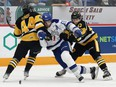 Chase Stillman, middle, of the Sudbury Wolves, attempts to skate between Nathan Staios, left, and Jonathan Melee, of the Hamilton Bulldogs, during OHL action at the Sudbury Community Arena in Sudbury, Ont. on Friday October 22, 2021. John Lappa/Sudbury Star/Postmedia Network