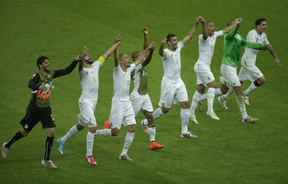 Members of the Algerian soccer team join hands as they celebrate on the pitch after winning 4-2 , the group H World Cup soccer match between South Korea and Algeria at the Estadio Beira-Rio in Porto Alegre, Brazil, Sunday, June 22, 2014. (AP Photo/Michael Sohn)